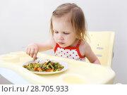 Купить «Happy little 2 years girl eating fish with vegetables», фото № 28705933, снято 30 июня 2018 г. (c) ivolodina / Фотобанк Лори