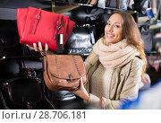 Купить «Ordinary girl choosing bag among assortment», фото № 28706181, снято 28 января 2020 г. (c) Яков Филимонов / Фотобанк Лори