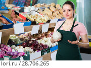 Купить «young saleswoman in store with onions in hands», фото № 28706265, снято 14 октября 2017 г. (c) Яков Филимонов / Фотобанк Лори