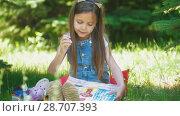 Купить «Cheerful little girl painting pictures with gouache on the grass in sunny day», видеоролик № 28707393, снято 17 июля 2018 г. (c) Константин Шишкин / Фотобанк Лори