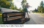 Купить «Case for violin lying on the bench in front of female who plays a fiddle at sunset», видеоролик № 28723321, снято 17 июля 2018 г. (c) Константин Шишкин / Фотобанк Лори