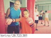 Купить «Girl at boxing workout on punching bag with coach», фото № 28723381, снято 12 апреля 2017 г. (c) Яков Филимонов / Фотобанк Лори