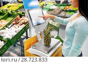 Купить «woman weighing pineapple on scale at grocery store», фото № 28723833, снято 2 ноября 2016 г. (c) Syda Productions / Фотобанк Лори