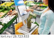 Купить «woman weighing pineapple on scale at grocery store», фото № 28723833, снято 2 ноября 2016 г. (c) Syda Productions / Фотобанк Лори