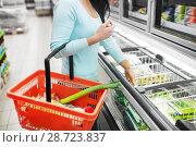 Купить «woman with food basket at grocery store freezer», фото № 28723837, снято 2 ноября 2016 г. (c) Syda Productions / Фотобанк Лори