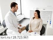 Купить «dentist talking to female patient at dental clinic», фото № 28723961, снято 22 апреля 2018 г. (c) Syda Productions / Фотобанк Лори