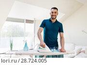 Купить «smiling man ironing shirt by iron at home», фото № 28724005, снято 10 мая 2018 г. (c) Syda Productions / Фотобанк Лори