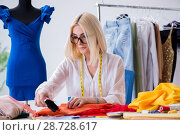 Купить «Woman tailor working on new dress designs», фото № 28728617, снято 13 апреля 2018 г. (c) Elnur / Фотобанк Лори