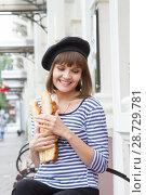 Купить «Молодая девушка сидит на скамейке и держит булки», фото № 28729781, снято 9 июля 2018 г. (c) Момотюк Сергей / Фотобанк Лори
