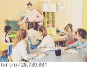 Купить «Teacher standing at blackboard in classroom», фото № 28730881, снято 28 января 2018 г. (c) Яков Филимонов / Фотобанк Лори