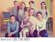 Купить «Portrait of friendly smiling group of pupils with female teacher», фото № 28730893, снято 28 января 2018 г. (c) Яков Филимонов / Фотобанк Лори