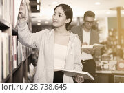 Купить «Girl searching textbooks in store», фото № 28738645, снято 18 января 2018 г. (c) Яков Филимонов / Фотобанк Лори