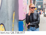 Купить «Woman talking on smartphone leaning against colorful graffiti wall in New York city, USA.», фото № 28738977, снято 31 марта 2020 г. (c) Matej Kastelic / Фотобанк Лори