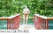 Купить «Young man gets out of the lake on the pier», видеоролик № 28751453, снято 16 июля 2018 г. (c) Константин Шишкин / Фотобанк Лори
