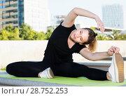 Купить «Young smiling girl practicing stretching outdoors», фото № 28752253, снято 5 июля 2017 г. (c) Яков Филимонов / Фотобанк Лори