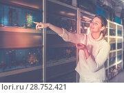 Купить «Girl in aquarium shop points to colored fish», фото № 28752421, снято 17 февраля 2017 г. (c) Яков Филимонов / Фотобанк Лори