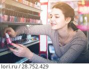 Купить «female customer looking for nail polish in cosmetics shop», фото № 28752429, снято 21 февраля 2017 г. (c) Яков Филимонов / Фотобанк Лори