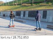 Купить «Девушка и юноша катаются на гироскутерах (ховербордах) по набережной Туры. Тюмень», фото № 28752853, снято 10 мая 2016 г. (c) Ольга Шуклина / Фотобанк Лори