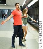Купить «Man with his girlfriend are standing on platform and waiting train», фото № 28753529, снято 14 июня 2018 г. (c) Яков Филимонов / Фотобанк Лори