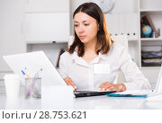 Upset woman working with laptop and papers at the office. Стоковое фото, фотограф Яков Филимонов / Фотобанк Лори