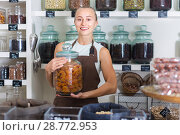 Купить «Young woman is offering dried apricot in container», фото № 28772953, снято 4 сентября 2017 г. (c) Яков Филимонов / Фотобанк Лори