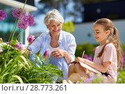 Купить «grandmother and girl study flowers at garden», фото № 28773261, снято 3 июня 2018 г. (c) Syda Productions / Фотобанк Лори