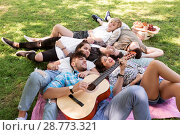 Купить «friends with guitar chilling on picnic blanket», фото № 28773321, снято 17 июня 2018 г. (c) Syda Productions / Фотобанк Лори