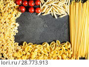 Купить «Dry pasta and tomates cherry background. Different pasta on dark background. Flat lay. Top view.», фото № 28773913, снято 25 апреля 2018 г. (c) Tetiana Chugunova / Фотобанк Лори