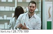 Купить «Young malepharmacist holding a white blank bottle of pills, promoting medicine, while his colleague working», видеоролик № 28779189, снято 6 апреля 2017 г. (c) Vasily Alexandrovich Gronskiy / Фотобанк Лори