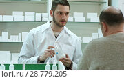 Купить «Young pharmacist advicing pills senior man customer at drugstore», видеоролик № 28779205, снято 6 апреля 2017 г. (c) Vasily Alexandrovich Gronskiy / Фотобанк Лори