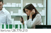 Купить «Bored female pharmacist use mobile phone at pharmacy», видеоролик № 28779213, снято 6 апреля 2017 г. (c) Vasily Alexandrovich Gronskiy / Фотобанк Лори