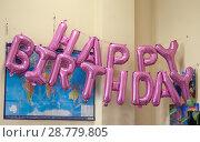 """В офисе на фоне прикрепленной к стене карты мира висят надувные буквы, составляющие надпись """"Happy birthday"""" (2018 год). Редакционное фото, фотограф Наталья Николаева / Фотобанк Лори"""