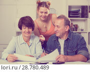 Купить «Smiling parents are reading utility bill with their adult daughter», фото № 28780489, снято 25 октября 2017 г. (c) Яков Филимонов / Фотобанк Лори
