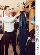Купить «Customer examining trousers», фото № 28780629, снято 28 марта 2017 г. (c) Яков Филимонов / Фотобанк Лори