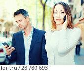 Купить «Couple strolling together and ignoring each other speaking on phones», фото № 28780693, снято 11 апреля 2017 г. (c) Яков Филимонов / Фотобанк Лори