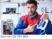Купить «Man repairman repairing iron at service center», фото № 28781009, снято 11 июля 2017 г. (c) Elnur / Фотобанк Лори