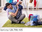 Купить «Handsome man husband doing laundering at home», фото № 28790105, снято 1 мая 2018 г. (c) Elnur / Фотобанк Лори