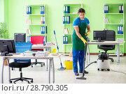 Купить «Handsome man cleaning office with vacuum cleaner», фото № 28790305, снято 31 мая 2018 г. (c) Elnur / Фотобанк Лори