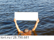 Купить «The man took his hands out of the water and held the poster», фото № 28790681, снято 1 сентября 2017 г. (c) Акиньшин Владимир / Фотобанк Лори