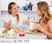 Купить «Two girlfriends are talking with tea and cake», фото № 28791197, снято 22 июля 2018 г. (c) Яков Филимонов / Фотобанк Лори