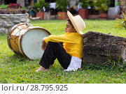 Купить «Young boy in Farmer's clothing hat covering his face sleeping sitting next to a drum.», фото № 28795925, снято 5 июля 2017 г. (c) age Fotostock / Фотобанк Лори