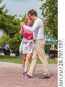 Купить «Russia, Samara, August 2017: a beautiful young couple dancing on the embankment of the Volga River on a summer hot day», фото № 28797197, снято 12 августа 2017 г. (c) Акиньшин Владимир / Фотобанк Лори