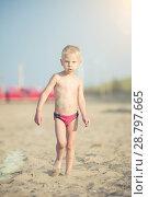 Купить «Cute baby boy walking on sandy beach near the sea. Ocean coast.», фото № 28797665, снято 24 июня 2014 г. (c) Александр Маркин / Фотобанк Лори