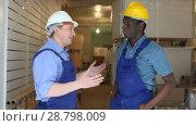 Купить «Confident builders discussing while examining room and planning construction works», видеоролик № 28798009, снято 21 мая 2018 г. (c) Яков Филимонов / Фотобанк Лори