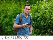 Купить «young man using mobile phone in the forest while hiking», фото № 28803733, снято 28 июня 2018 г. (c) Иван Карпов / Фотобанк Лори