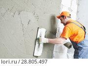 Купить «Renovation at home. Plasterer spreading plaster on wall.», фото № 28805497, снято 2 апреля 2018 г. (c) Дмитрий Калиновский / Фотобанк Лори