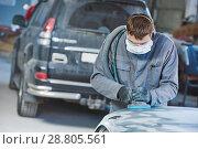 Купить «auto repairman grinding autobody bonnet», фото № 28805561, снято 15 марта 2016 г. (c) Дмитрий Калиновский / Фотобанк Лори