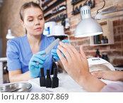 Manicurist girl polishing nails to female client in salon. Стоковое фото, фотограф Яков Филимонов / Фотобанк Лори