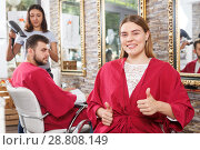 Купить «Smiling young woman client in salon's peignoir holding thumbs up», фото № 28808149, снято 25 апреля 2018 г. (c) Яков Филимонов / Фотобанк Лори