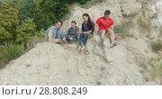 Купить «Young happy friends sitting on the mountain and enjoying recreation in nature», видеоролик № 28808249, снято 11 июля 2020 г. (c) Константин Шишкин / Фотобанк Лори